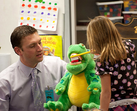 Dr. Kvinsland works with a 1st grader, brushing a (stuffed animal) dinosaur's teeth.